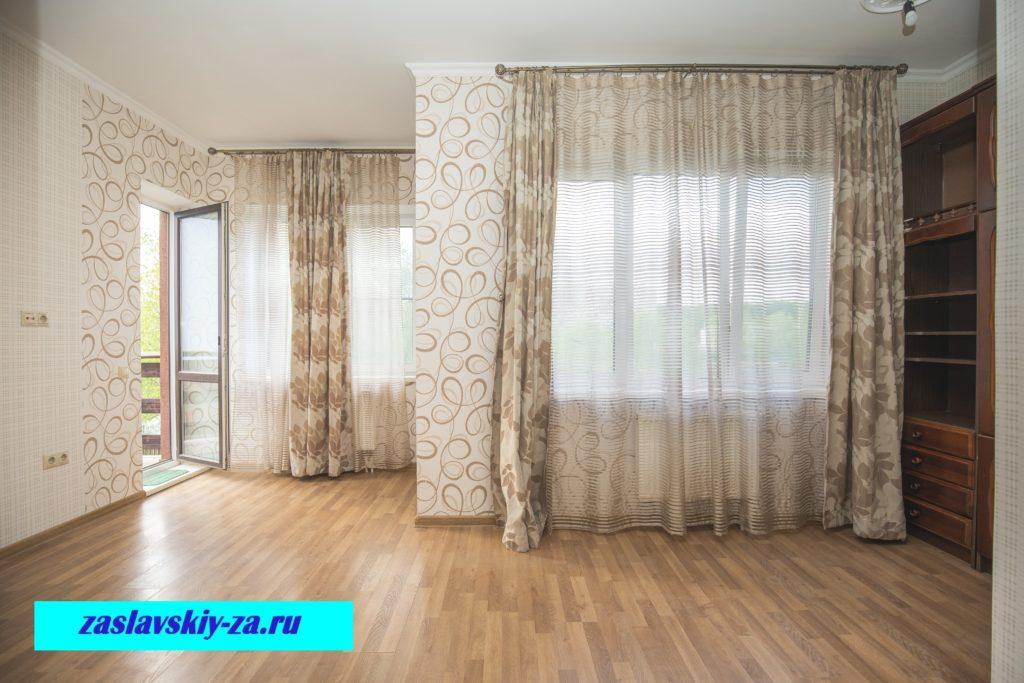 Жилая комната таунхауса с балконом и окнами на водоем